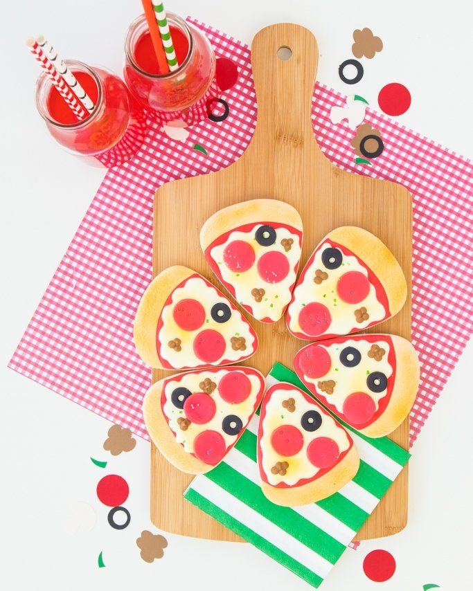 Pizza cookies for a pizza party on pizza board and drinks around - pizza party ideas using toppings cutouts