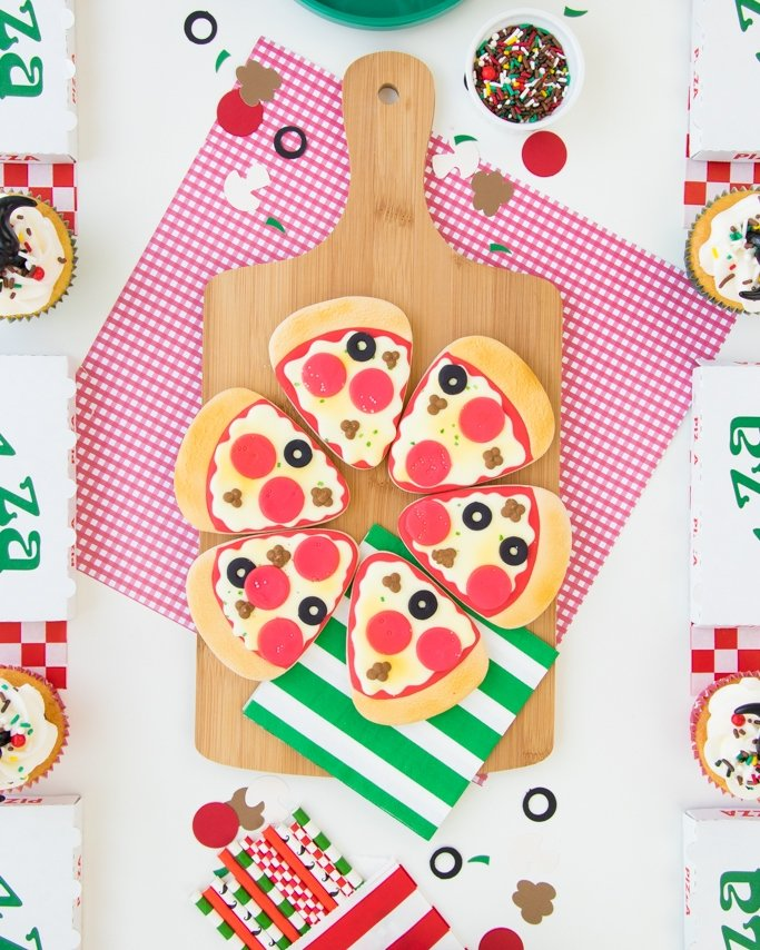 pizza party table with pizza slice cookies in center of table