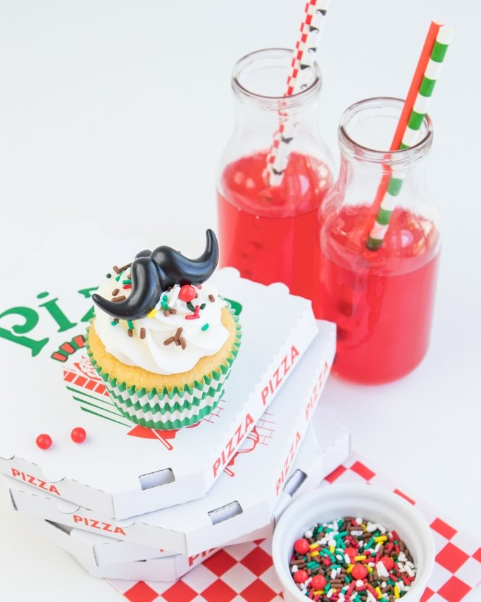 Pizza party cupcake topped with pizza sprinkles and drinks.