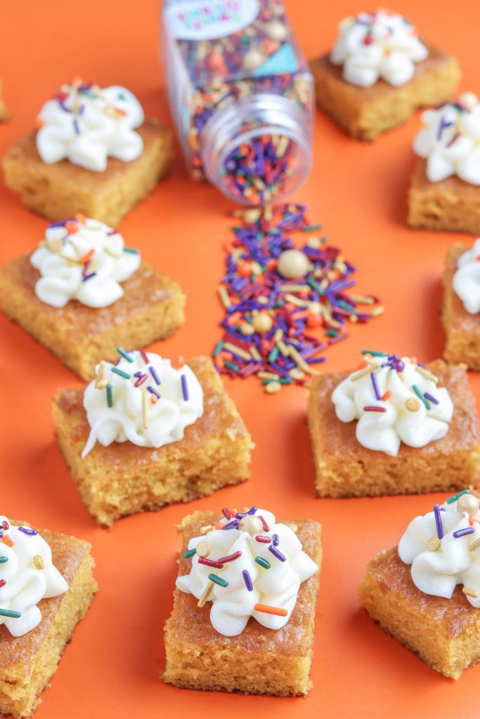 side view of pumpkin bars and fall sprinkle on orange background