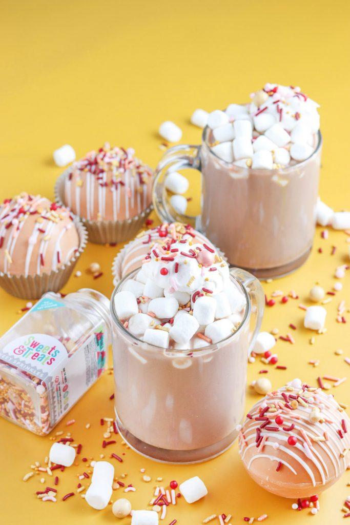side view of mugs of fall hot chocolate bombs recipe