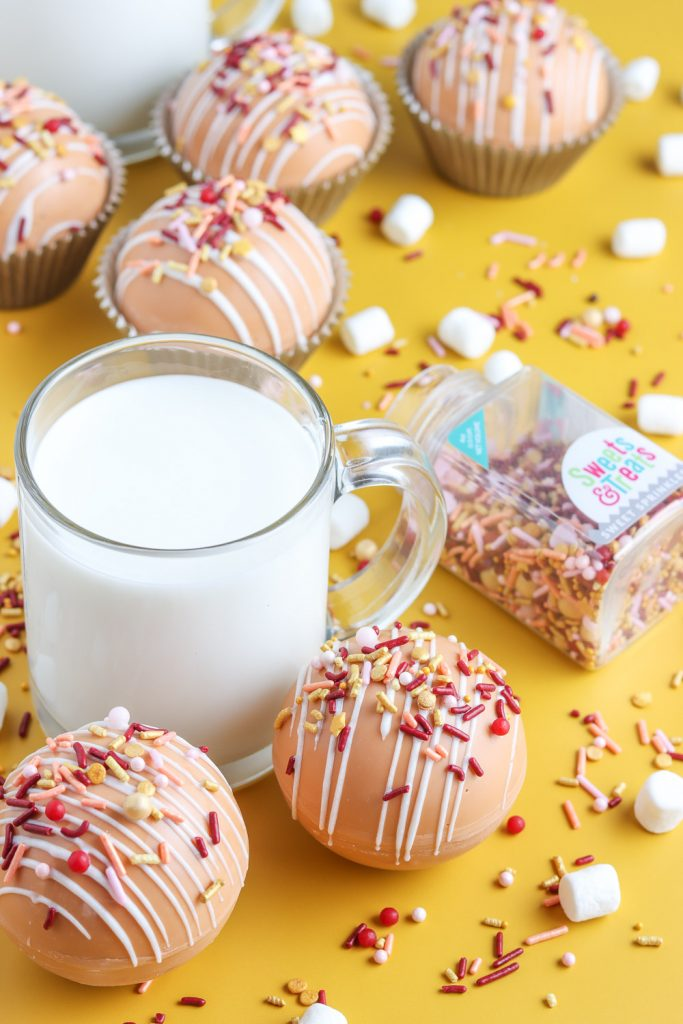 side view of hot cocoa bombs with milk