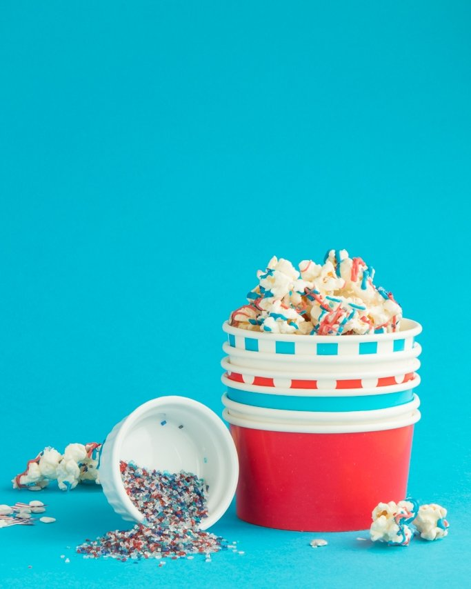 Patriotic Popcorn - Easy 4th Of July Snack in red, white, and blue ice cream cups on blue background with sprinkles poured out