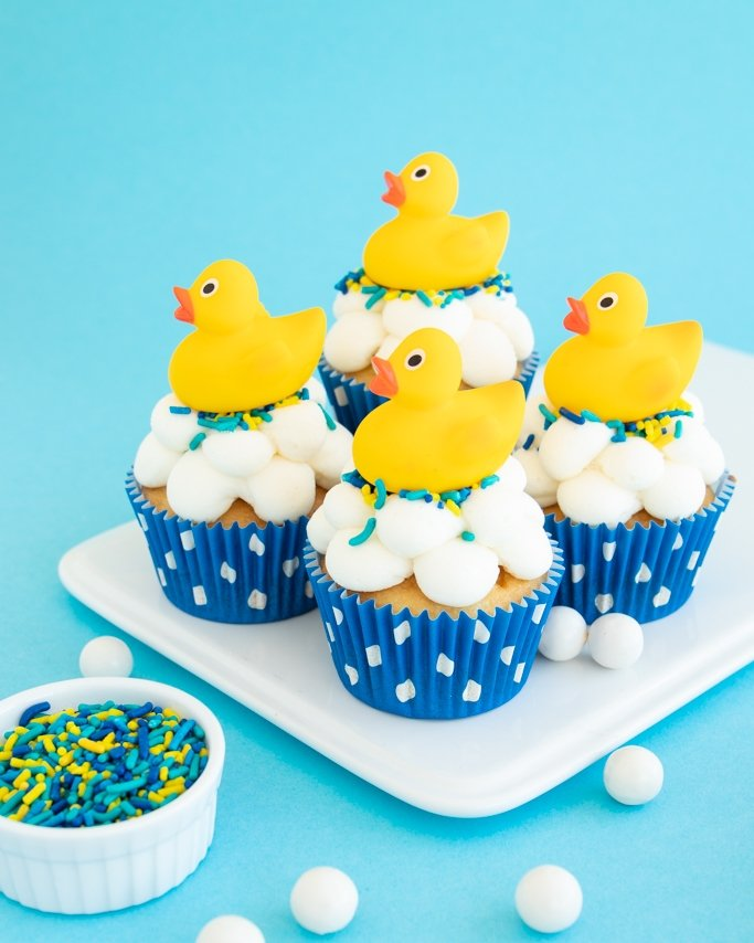 Rubber Ducky Baby Shower Ideas - Rubber Duck Cupcakes with rubber ducks on top on white plate