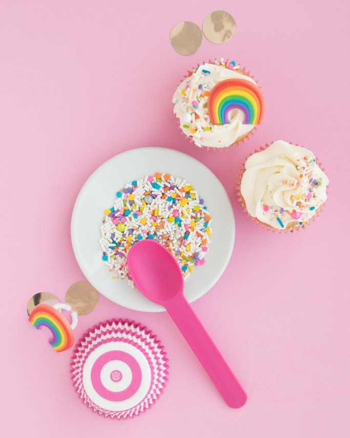 Best Cupcake Frosting Recipe on rainbow cupcake with unicorn sprinkles on pink background