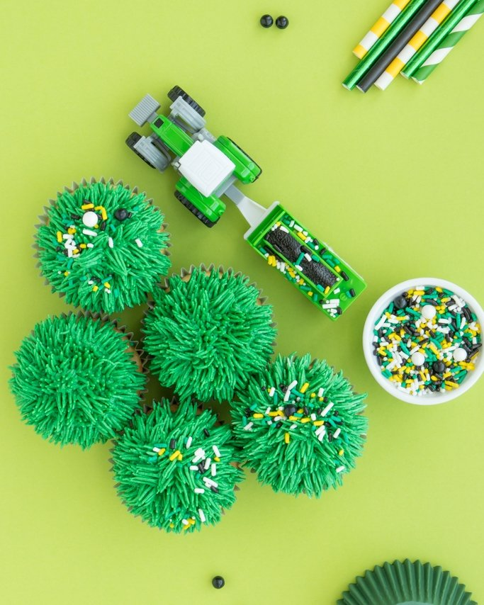 Grass cupcakes with tractor birthday party sprinkles on lime green background