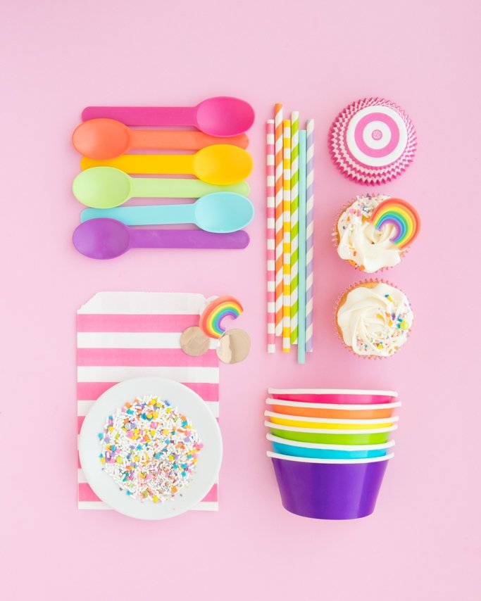 Rainbow party supplies collage with ice cream spoons, ice cream cups, paper straws, and rainbow sprinkles on light pink background