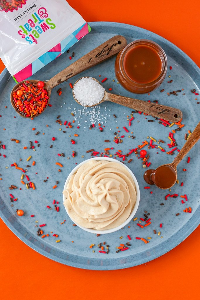 overhead photo of caramel icing recipe on round metal platter, ready for fall desserts