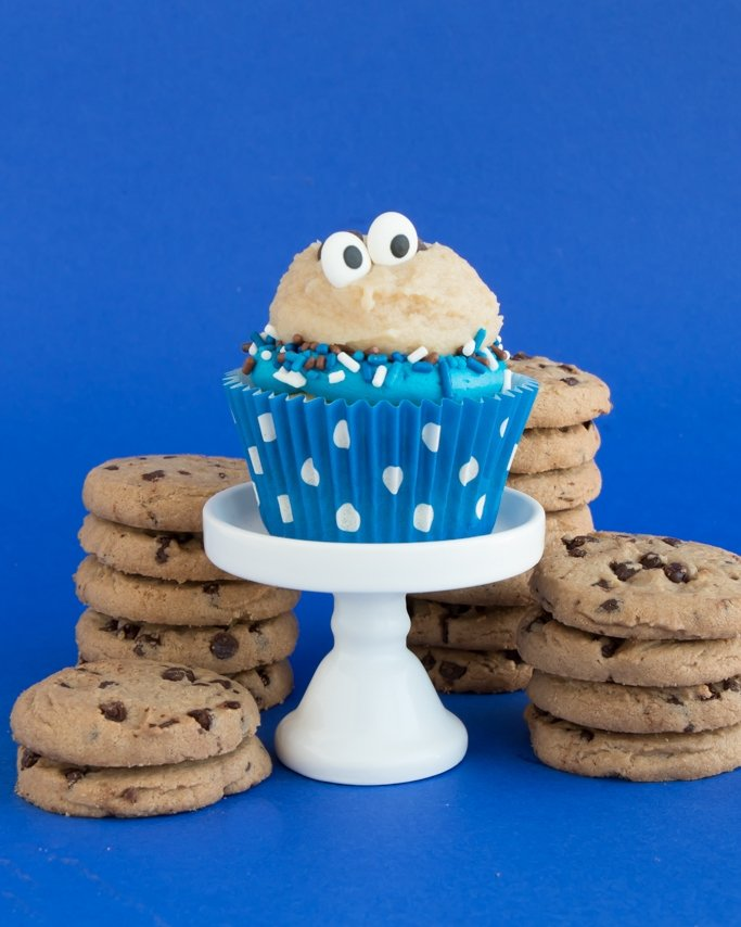 Cookie Dough Frosting Recipe - Cookie Monster Cupcakes on blue background and cookies stacked behind