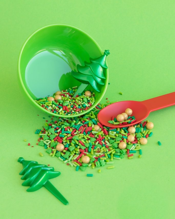Christmas Sprinkles and Christmas Baking Supplies on green background