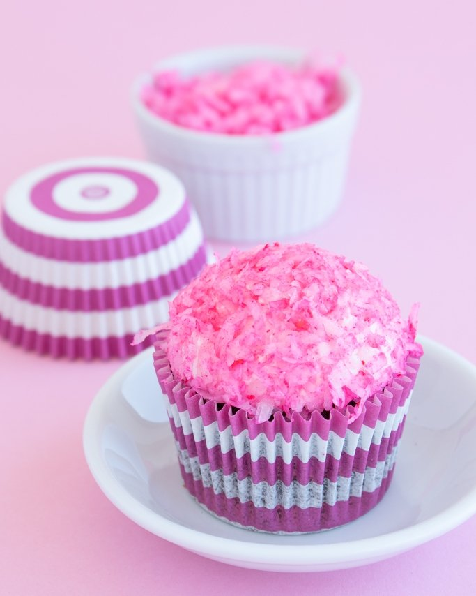 coconut cupcakes with marshmallow frosting, copycat snoball cupcakes on white dish topped with pink shredded coconut on chocolate cupcakes