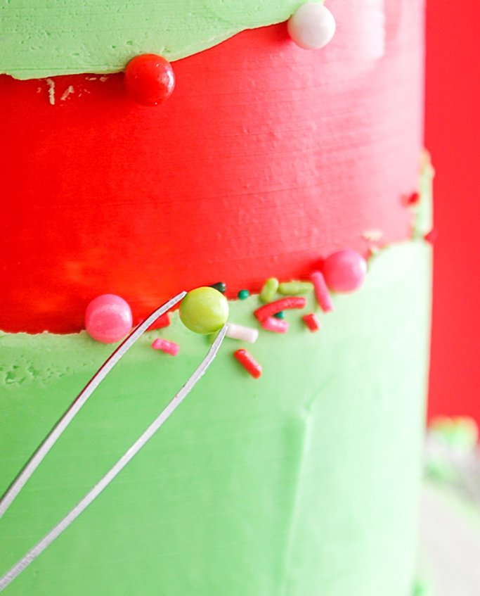 using tweezers, add larger sprinkles to fault line cake