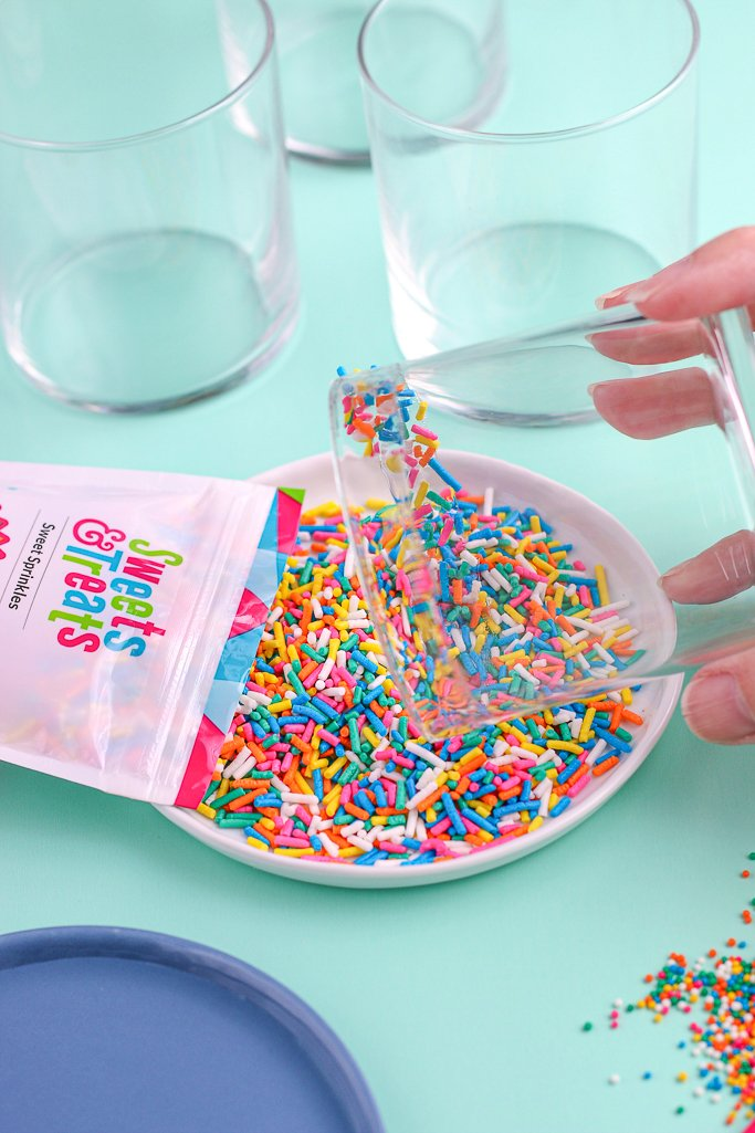 Now we just roll the glass in sprinkles as we complete the final step in the tutorial for how to rim a glass.