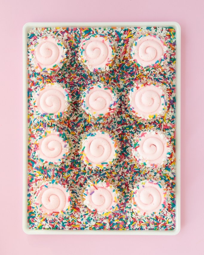 sprinkle rimmed swirl cupcakes on plate of sprinkles