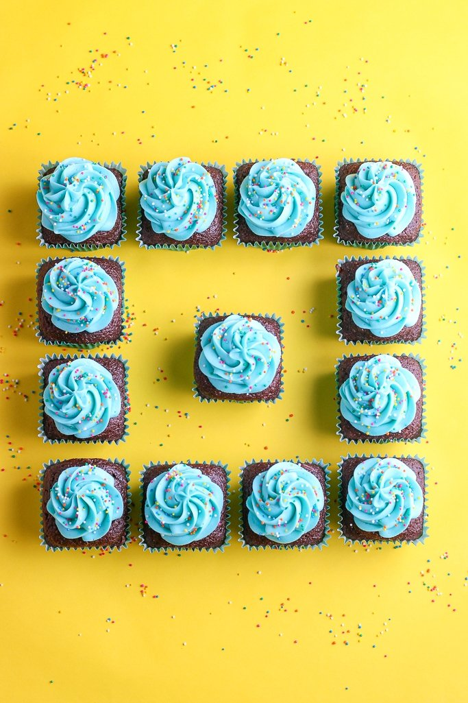 This is a great image of the finished and decorated square cupcakes against a bright yellow background looking festive and tasty.