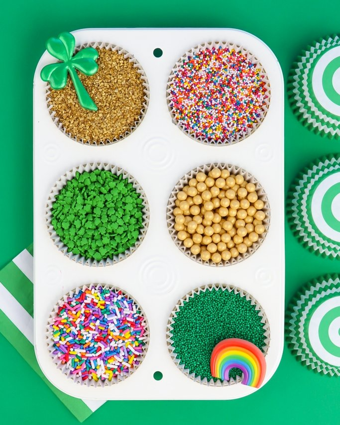 St. Patrick's Day Sprinkles in cupcake pan on green background