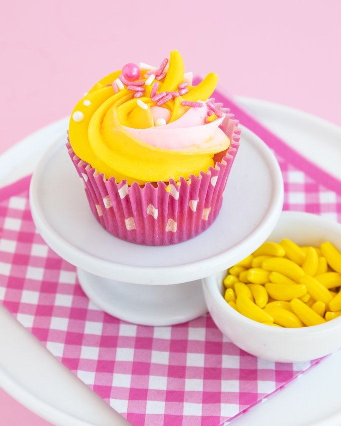 strawberry banana cupcake with banana candies on white cupcake stand