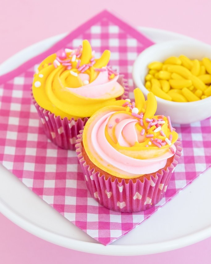strawberry banana cupcake recipe with swirl frosting and banana candies in dot pink cupcake liners