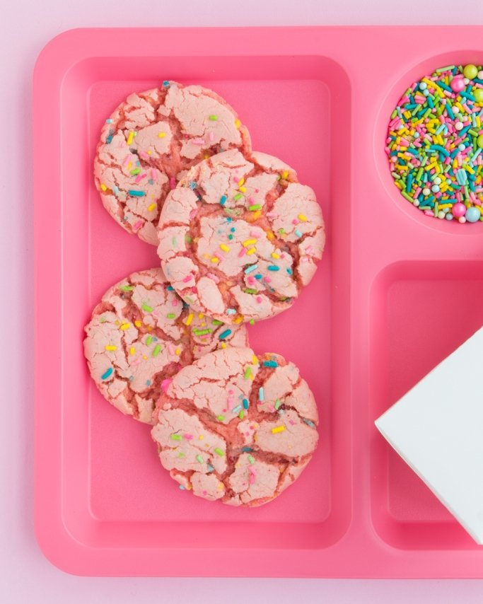 Strawberry Cake Mix Cookies with cake sprinkles on pink school plate