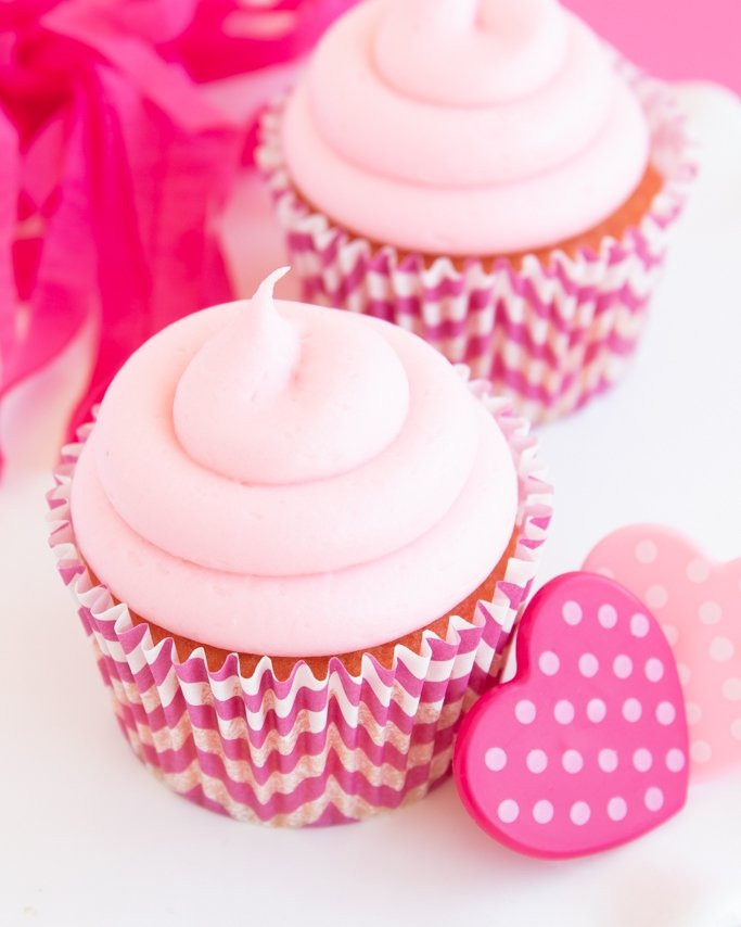 closeup of strawberry cheesecake cupcakes with cream cheese frosting and heart ring topper