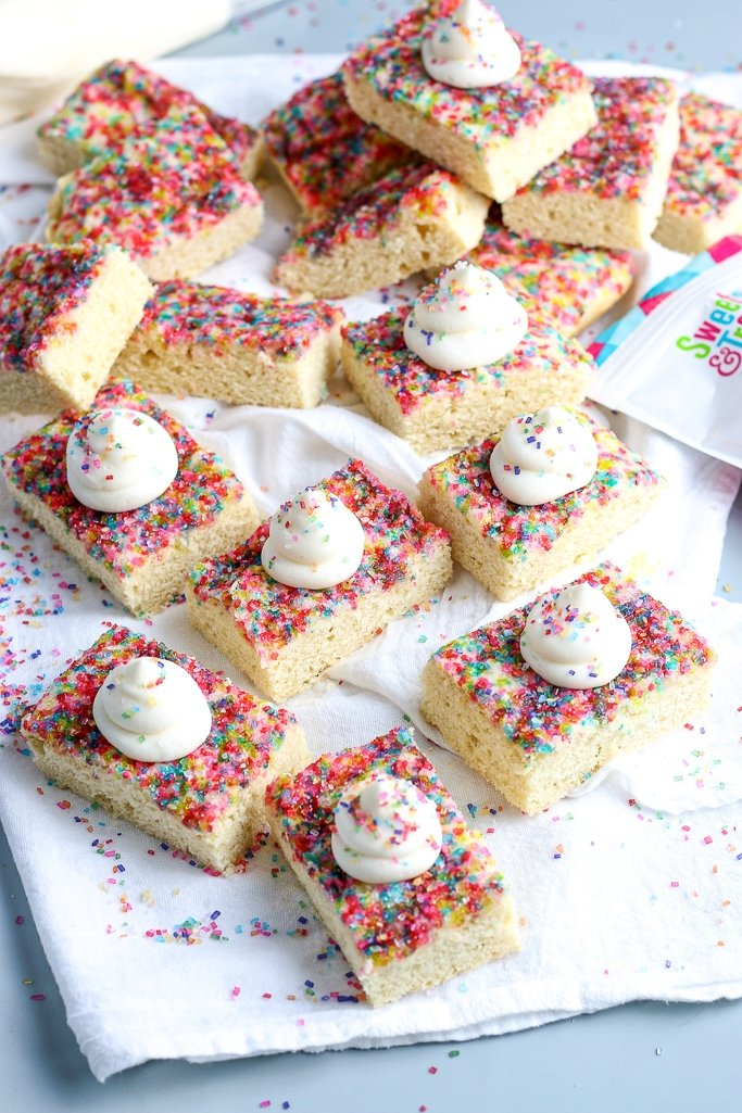 table full of sugar cookie bars with sprinkles and buttercream frosting on top