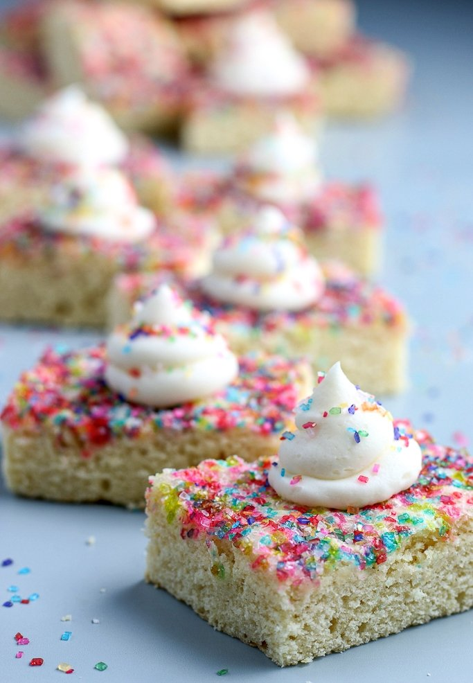 closeup of sugar cookie bars with frosting and sprinkles on top