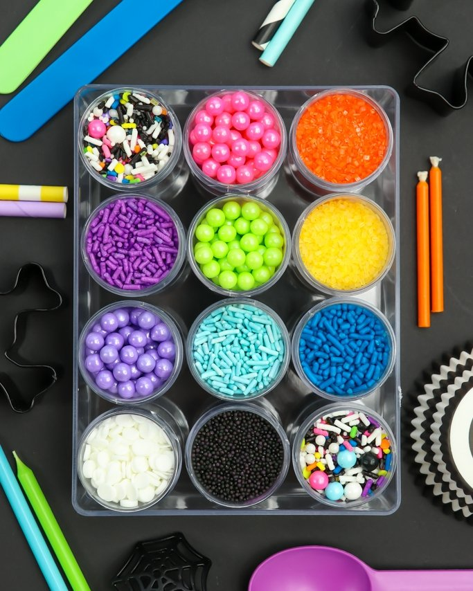 Day of the Dead Party Ideas sprinkle kit around Halloween party supplies on black background