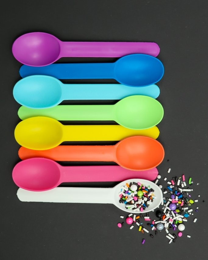 Rainbow Plastic Reusable Ice Cream Spoons - Day of the Dead Party Supplies with sugar skull sprinkles on black background