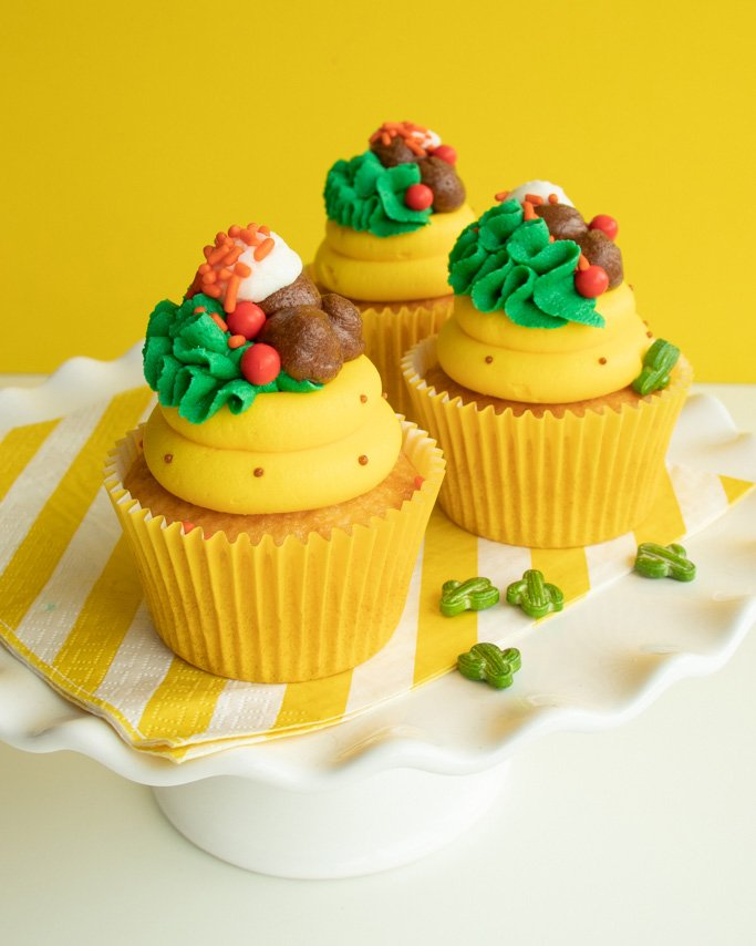 plate full of taco cupcakes with buttercream topping on yellow striped napkin