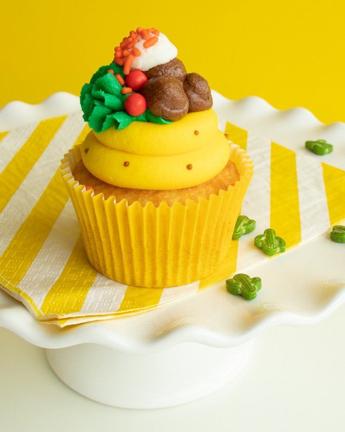 closeup shot of taco cupcakes with piped toppings in buttercream and sprinkles