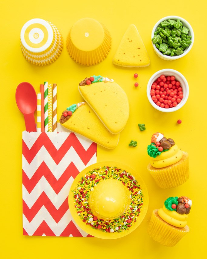 Taco Party Ideas, Taco Party Supplies laid out on yellow background around taco cookies and taco cupcakes