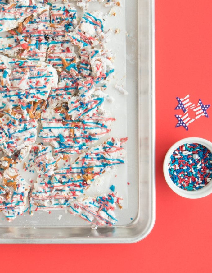 Easy 4th of July Dessert - Patriotic Trail Mix Bark on silver pan next to sprinkles on red background.