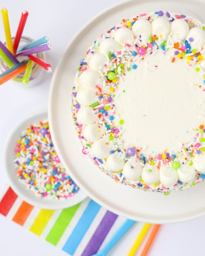 Super Simple Sprinkle Covered Rainbow Cake - Fast and easy personal sprinkle rainbow cake using leftover batter and one of our best selling sprinkle mixes, Unicorn Cake. Frost the top and sprinkle the sides for a beautiful sprinkle cake people will think you spent so much time on! Sweet buttercream and delicious sprinkles you'll love!