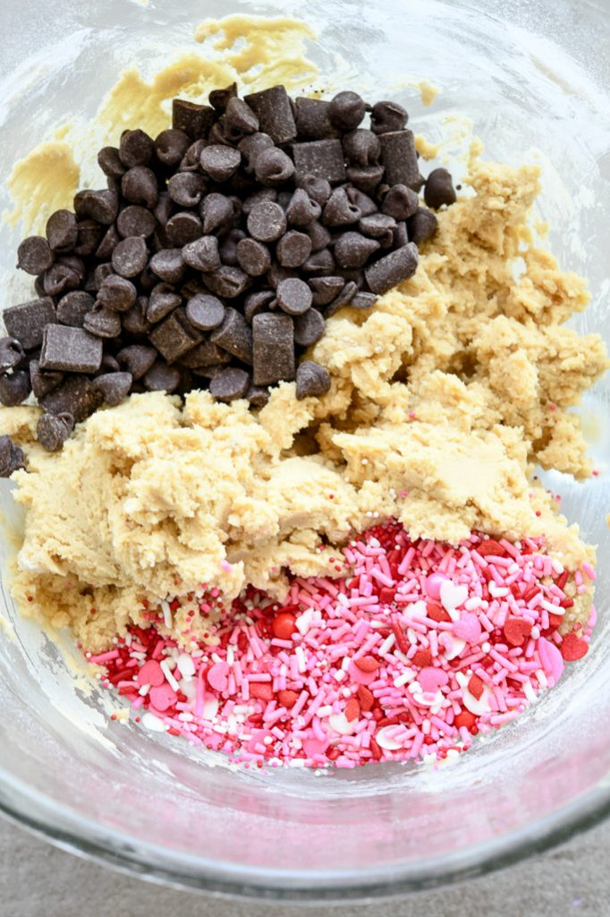 Chocolate chip cookie dough in clear mixing bowl with valentine sprinkles