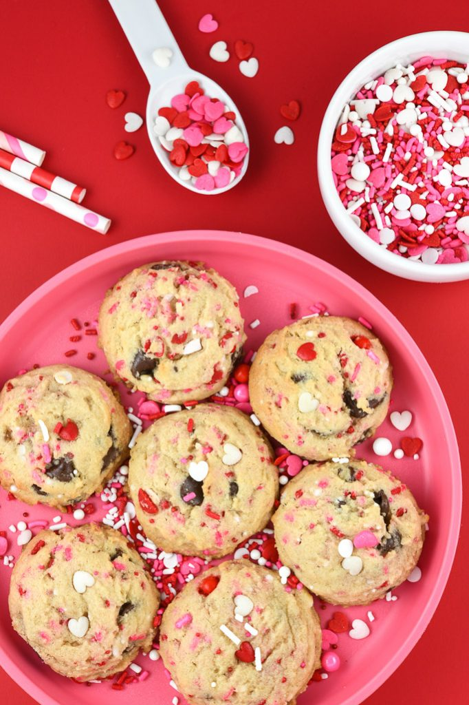 valentine chocolate chip cookies on pink plate with sprinkles around