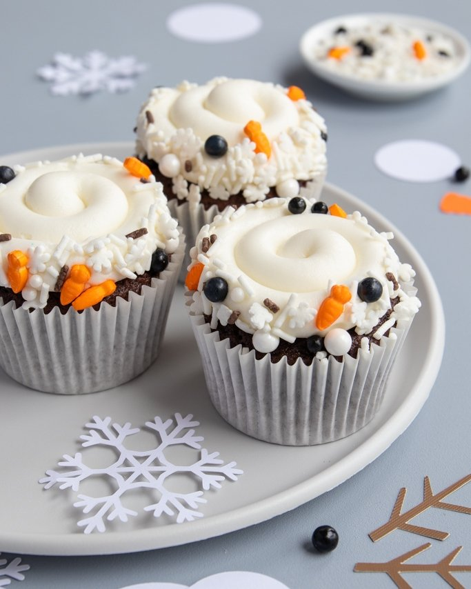 plate of melted snowman cupcakes with melted snowman sprinkles on rim