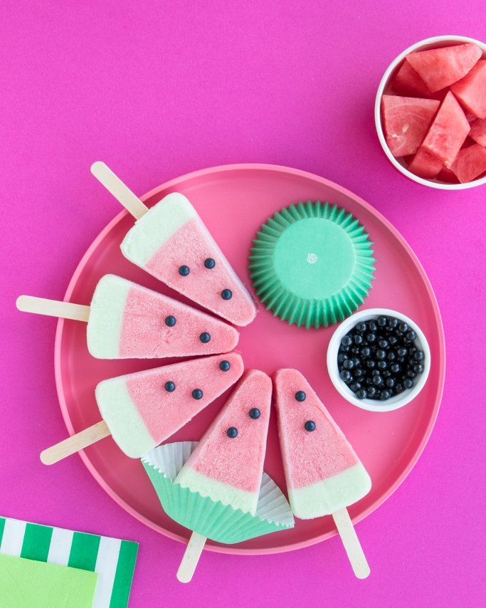 Watermelon popsicles on pink plate with black sugar pearls on top for seeds