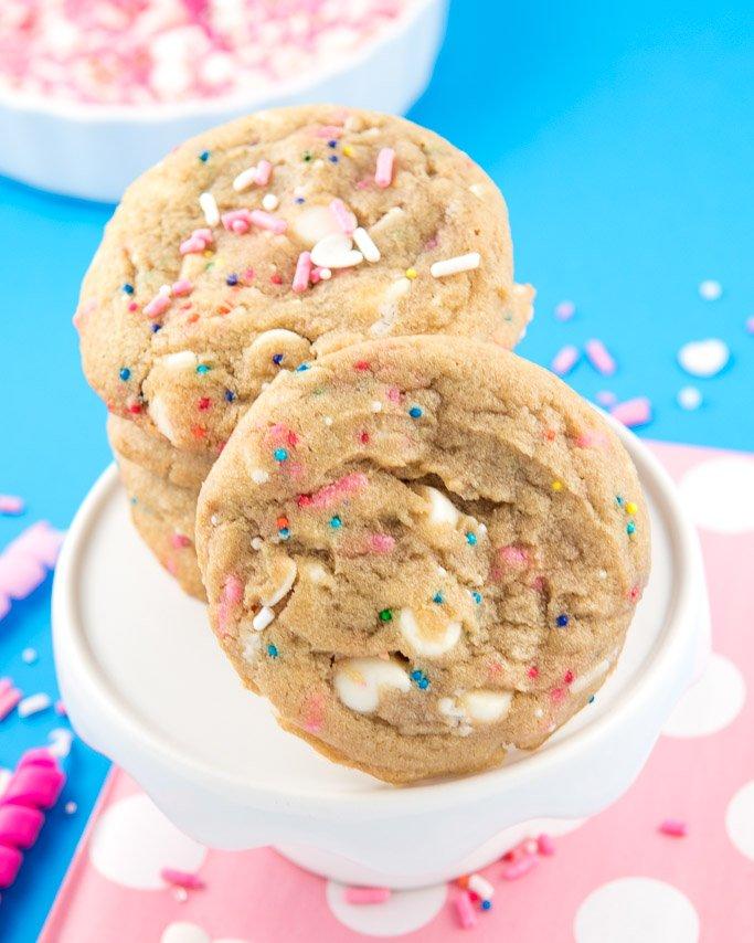 Closeup of white chocolate circus cookies on white mini cake stand