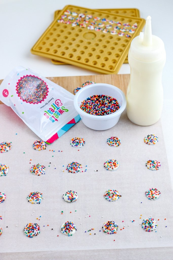 The melted chocolate for our nonpareils candy gets piped out onto the wax paper before we add the colorful nonpareils.